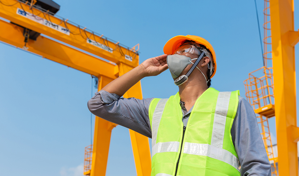 man wearing hard hat and face mark on building site