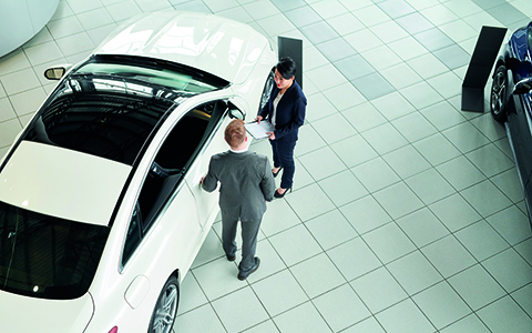 Car showroom with two men talking next to a car
