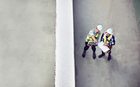 birds eye view of two men with hard hats pointing to something