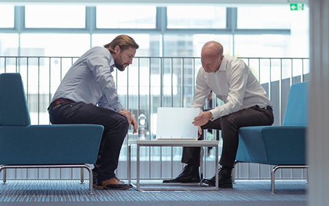 Businessmen talking over coffee table