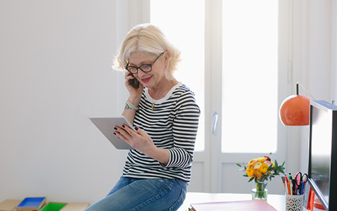 lady sitting on desk looking at smart device