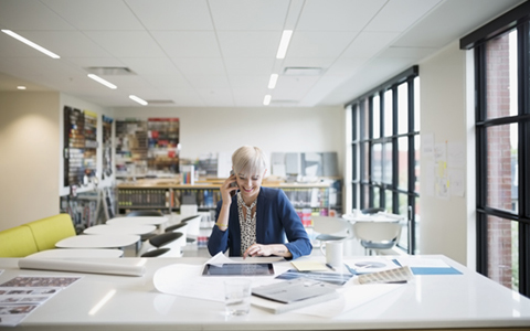 woman sat in a bright and airy office on the phone and reading a document