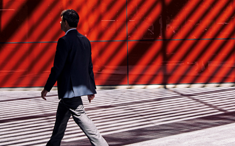 person walking infront of a red building