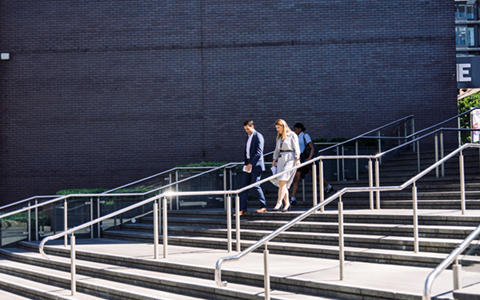 two people walking down a set of external stairs