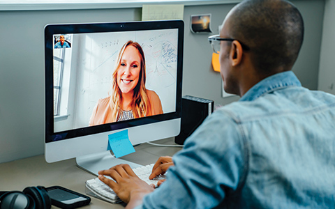 man speaking to colleague over video conference