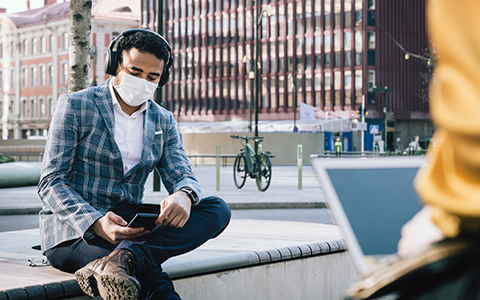 man sitting on city bench with face mask on looking at his phone, Supporting Mental Health in the Workplace Post COVID-19