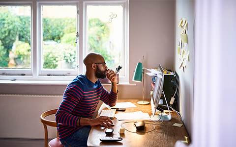 man working from home next to window