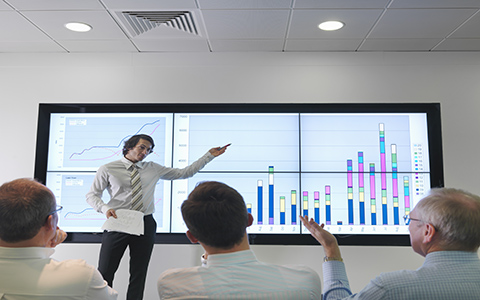 person presenting graph to co-workers